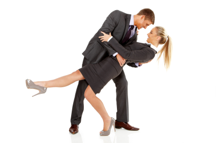 Happy young business couple dancing against white background